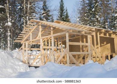 new Christmas wooden house at pine forest background. winter time forest. Wooden cottage near the pine forest, covered in snow. frame of modern bio eco house under construction