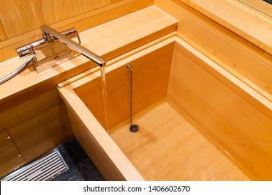 New clean cypress bathtub wooden traditional Japanese tub in home house or onsen hotel bathroom interior with nobody and running water in Japan