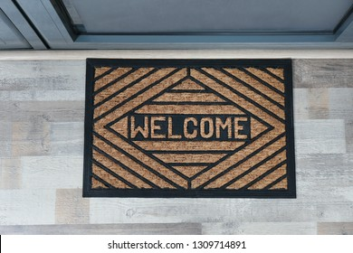 New clean mat with word WELCOME near entrance door, top view