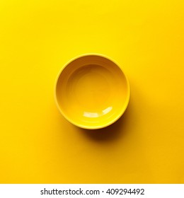New clean yellow bowl on yellow background. Top view