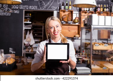 New coffee shop owner standing with blank screen tablet in her hands
