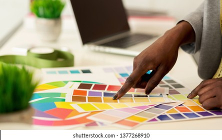 New collection. Fashion designer choosing colors, pointing on swatches pallet, closeup