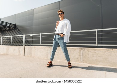 New collection of fashionable summer menswear. Attractive young hipster man in stylish clothes in vintage sunglasses with a hairstyle with a bag in sandals poses in the city on a sunny summer day.