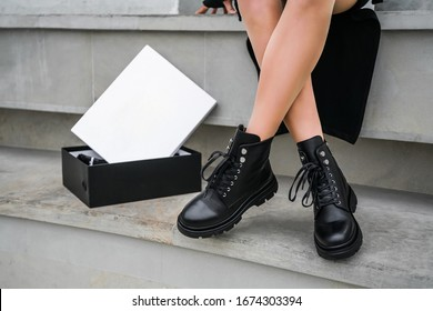 a new collection of women's shoes autumn winter '20 / 21. The girl bought new shoes. Legs in black boots. Boots in a box