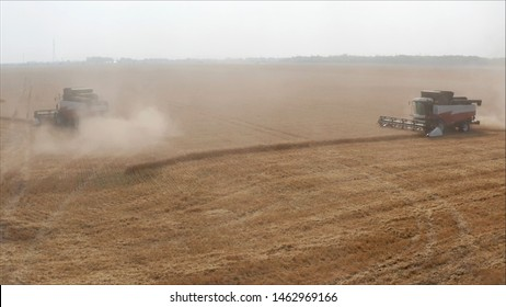 A new combine in a field. Combines harvested wheat from the fields. An agricultural combine harvests grain or wheat in a field.