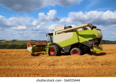 New combine turning on headland, grain harvest during hot summer day with blue cloudy sky on background, side perspective, fertilized barley field, bio agriculture