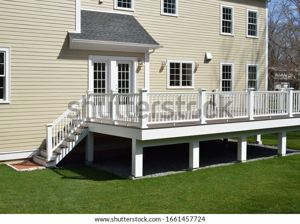 New composite deck. White veranda and railing posts, brown boards, elevated above ground. Showing support frame and gravel under porch.