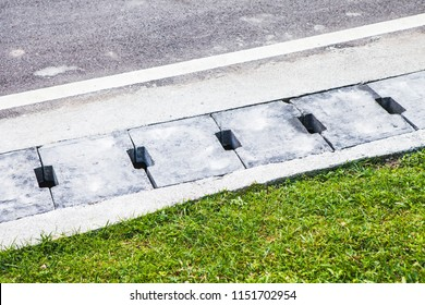 New Concrete water drain cover or ditch on the road with green grass