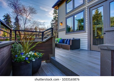 New construction home exterior boasts luxury oversized deck overlooking a Well-designed garden.