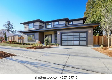 New construction home exterior with contemporary house plan  features low slope roof, brown siding and glass garage door. Northwest, USA