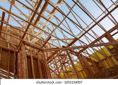 New construction home framing against blue sky, closeup of ceiling frame.