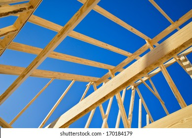 New construction home framing against blue sky, closeup of ceiling frame.