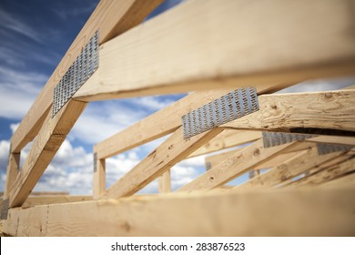 New construction home framing against a blue sky and sun