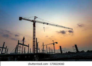 New construction site with cranes on orange sunset, sunrise sky background. Steel frame structure, structural steel beam build large buildings at construction site . construction machinery. - Shutterstock ID 1730224360