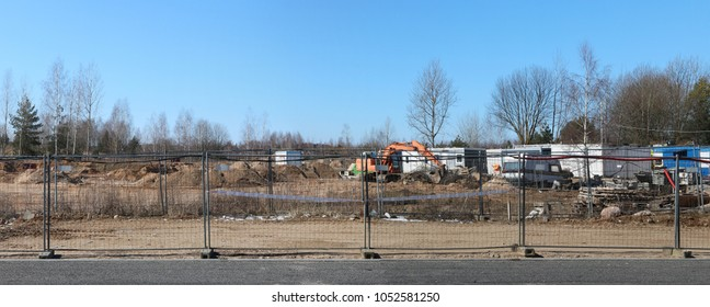 A new construction site in the spring forest. Beginning of the construction of a large shopping center. Panoramic collage from several photos. All logos removed.