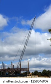 New construction is using a crain for the heavy lifting.  Workers operate machinery.  Blue sky frames site.