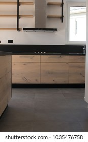 New crafted kitchen in wood, stainless steel and black granite just set up in a new apartment. Interior industrial design with exposed shelves and dark gray floor. Oak wood, black color and inox steel