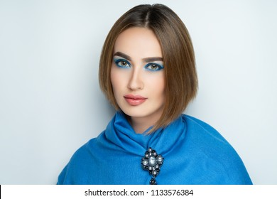 New creative make-up, conceptual idea. Blue shadows, vivid colors graphic shapes lines, art cosmetics paints, colorful wow brooch jewellery. close-up photo. skin painting artistic. perfect lips shape