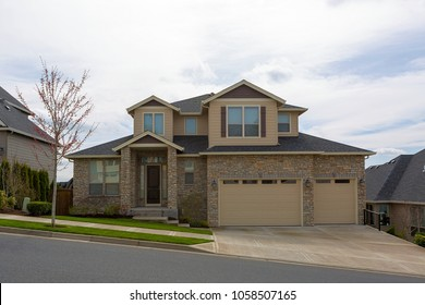 New custom built upscale house in Happy Valley Oregon suburban neighborhood with cultured stone exterior and three car garage