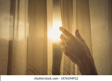 New day and new beginnings, rise and shine concept. Hand opening up window curtain letting the early morning sunshine in.