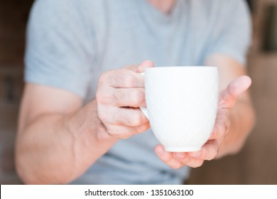 New day. Morning wake up drink. Coffee time. Man offering white cup of energy beverage.