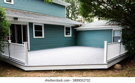 A new deck is installed on the back of a house with composite material and white hand rails.