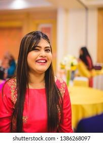 New Delhi, Delhi, India 01/22/2019 : A girl in red dress smiling mischievously