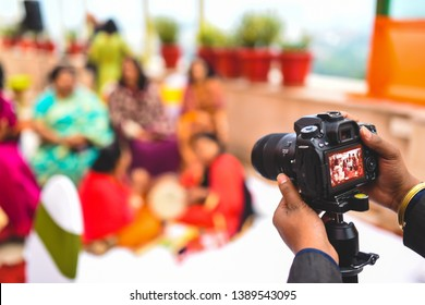 New delhi, Delhi, India 01/24.2019 : A camera on a mono pod taking picture of a group of women singing at a wedding.