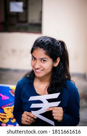 New Delhi, Delhi, India - 02/04/2016: A beautiful Indian girl smiles while holding the symbol of Indian National Rupee. A college student creates an Indian currency symbol with white paper.