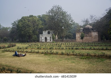 New Delhi, India - 02.05.2014: Man taking rest on grass in Lodi gardens park with monuments in the background.
