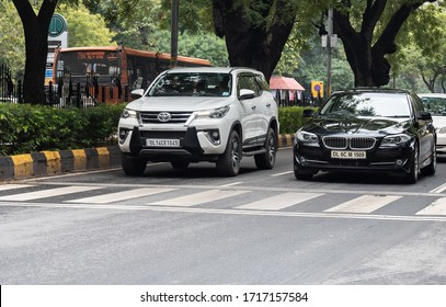 New Delhi, Delhi, India - 03/07/2019: Two expensive luxury cars on Indian streets in the capital city. Growing number of vehicles on road in the premium sedan and SUV personal transport segment.