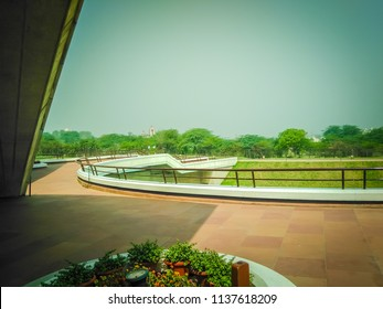 New Delhi, Delhi, India; 04 14 2017: View of the beautiful green gardens with tall palm trees, and other plants of the famous Lotus temple, a white floral shaped building, in New Delhi, India, Asia.