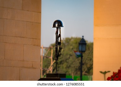 """New Delhi, Delhi / India - 04/25/2018: An inverted rifle is placed on the top of a podium. The Hindi word """"Amar Jyoti"""" states """"Solider always Live"""". It is situated under the most famous monument."""