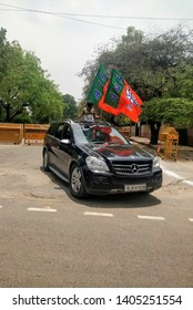 new Delhi/ India : 05 23 2019 : kid celebrating the win of BJP with flying two flags of BJP from sunshade of a Mercedes car