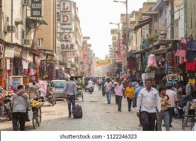 New Delhi / India - 06 21 2018: A man walking with a roller suitcase down a crowded Main Bazar in New Delhi during a hot summer afternoon.
