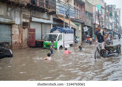 New Delhi / India - 07 16 2018: Children playing in the water masses of the latest rain in the center of the city while a cycle rickshaw is trying to pass on the street.