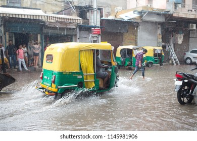 New Delhi / India - 07 20 2018: Heavy rainfall in Delhi causes floods that is a problem for transportation as auto rickshaws try to drive through the water masses.