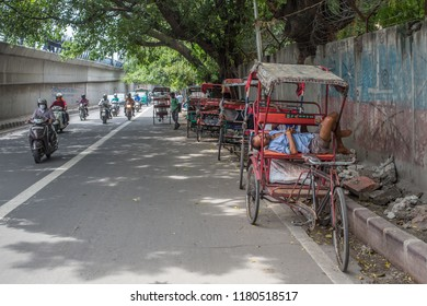 New Delhi / India - 07 20 2018: Rickshaws with some drivers resting on the side of the road during a hot summer day in the center of New Delhi.