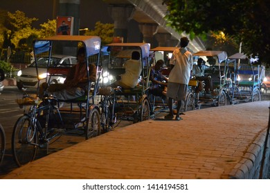 New delhi, Delhi, India - 09/05/2014 : A main street at night filled with rickshaw pullers waiting for their customers.