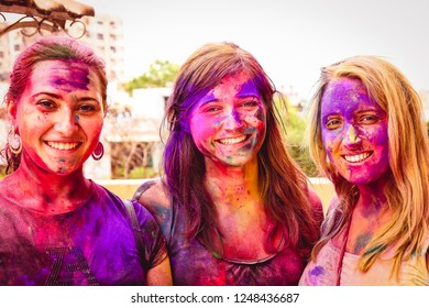 New delhi, India - 10 march 2016: close up portrait of young, happy eurpean girls with big smile and face full of coloured powder looking in camera during holi festival