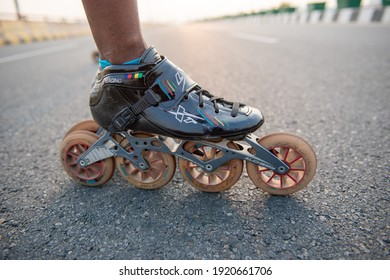 New Delhi, India, 17 February 2021: Close up picture of rollerblades, unknown person skating on road with rollerskates to spend time actively,