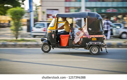 New delhi, India - 20 may 2018: panning of young indian rickshaw driver in the street with passenger in traditional sari. Rickshaw is the most popular mean of transport among common people