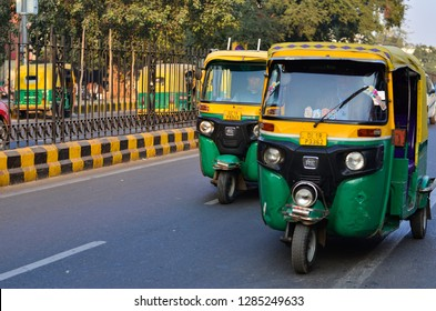New Delhi, India, 2019. 2 auto rickshaws racing in city. These CNG fueled autos is a popular urban transportation on Indian roads, Mumbai, Pune, Lucknow, Hyderabad, Bangalore, Chennai, Noida, Gurgaon
