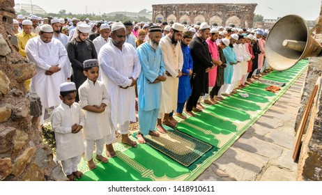 New Delhi, India - 5th June 2019: A gathering of Muslim men and children offering Namaz prayers on the occasion of Eid'Al-Fitr. They were dressed in traditional kurta-pyjamas and wearing skullcaps.