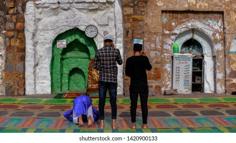 New Delhi, India 5th June 2019: 3 friends seen offering traditional Namaz prayers on the occasion of Eid-Al-Fitr at a mosque in New Delhi. They are all wearing the traditional muslim white skullcap