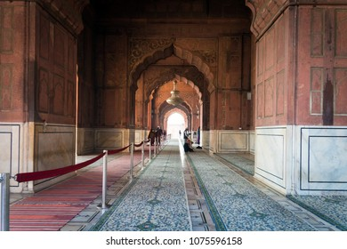 NEW DELHI, INDIA - 8 JANUARY 2018: Jama Masjid in details. The prayer hall in the mosque. Muslims during prayer. Carved arch on the background.