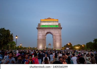 New Delhi, India - April 2019 : India Gate in evening with twilight sky and crowd of local people and tourist visit.  The India Gate is a war memorial located astride the Rajpath.