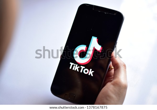 New Delhi, India - April 23, 2019: girl holding phone with  streaming service media and video TikTok application on the screen, banned by the indian goverment