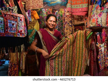 NEW DELHI, INDIA : April 3, 2016 : Unidentified Indian woman selling scarf in night market. Indian textiles handmade are popular in the world.