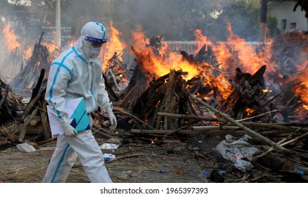 New Delhi, India, April 30, 2021: Mass cremation COVID 19 death. A relative wear PPE kit seen during the mass cremation of those who died from the coronavirus disease COVID-19 at a crematorium
